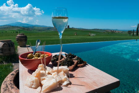 Closeup view of a traditional appetizer serving dish on a magnificent swimming pool in the Tuscan countryside