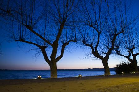 The nice lake promenade of Trevignano Romano, a nice village on Bracciano lake, near Rome, Italy, at the dusk, in winter Standard-Bild