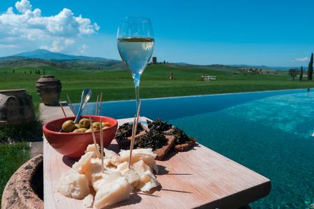 Nahaufnahmeansicht eines traditionellen Aperitifserviertellers auf einem ausgezeichneten Swimmingpool in der toskanischen Landschaft Standard-Bild - 87746720