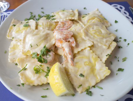 Nahaufnahme eines typischen Tellers der italienischen Meeresfrüchteküche selbst gemacht mit aufgefüllten Teigwaren, weißer Soße und kleinen Garnelen Standard-Bild - 87739218