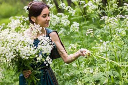 gathers: the girl in the dress gathers flowers Stock Photo