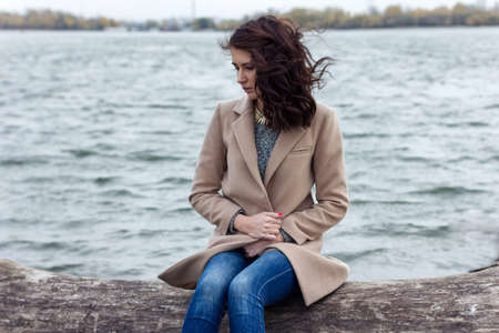 greatcoat: portrait of a sad girl sitting near the water
