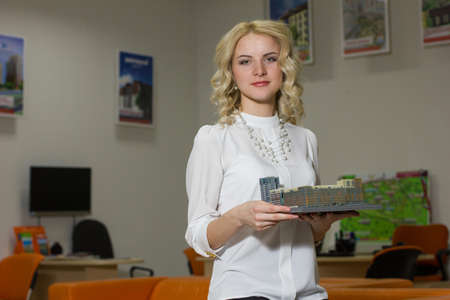 first time buyer: portrait of a cute girl realtor in office Stock Photo