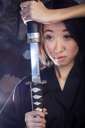 samurai sword: Beautiful geisha in kimono with samurai sword