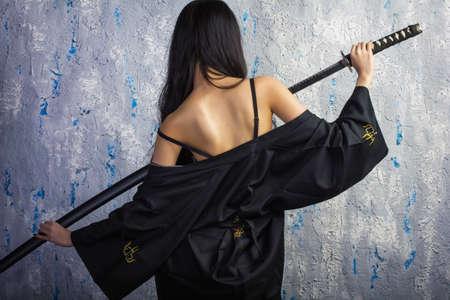 Beautiful geisha in kimono with samurai sword