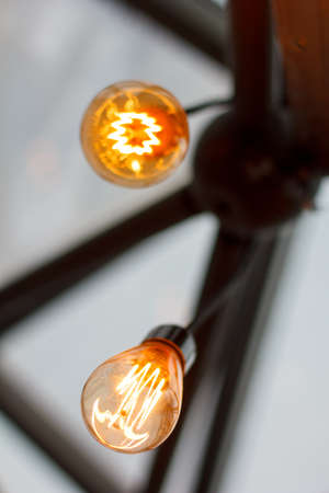 Old Style Glowing Light Bulbs Hanging in Restaurant. Stock Photo