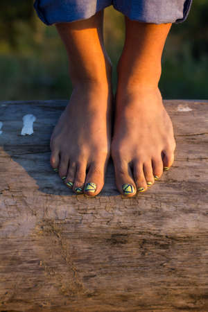 noon: legs beautiful girls on the balance beam with a pedicure Stock Photo