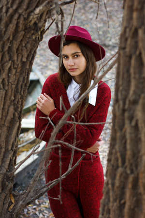 the girl walks in autumn woods in the hat