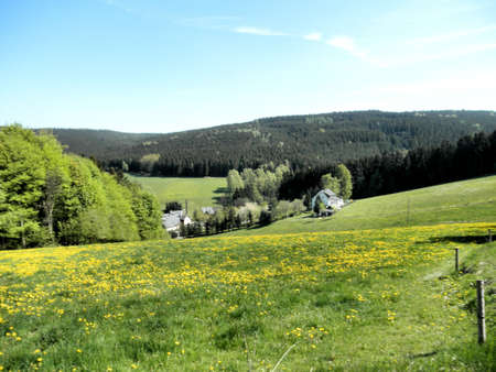 Idyllic landscape in the Erzgebirge in Germany. Rolling hills, spring, woods and  meadows, scattered houses photo