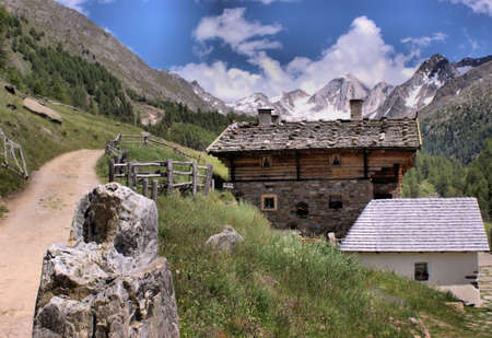 An alpine hut in the small Pfossental in the nature park Texel Group. In the background the snow-capped peaks Hohe Weise and the Lodner. photo