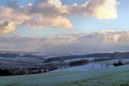 cloud formation: First snow in the Erzgebirge, idyllic winter landscape, snow-covered fields, forests and villages, evening mood with an interesting cloud formation