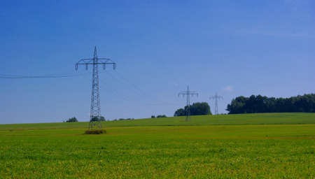 Transmission lines, power lines, a green field and blue sky photo