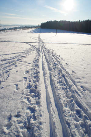 Traces in the snow; against the sun, ski- and foot tracks on a snowy field photo