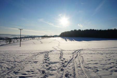 Against the sun; tracks on a snowy field, sun and blue sky photo