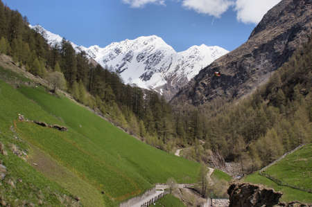 On the Merano High Mountain Trail in South Tyrol, Italy; mountain tour on a sunny day in the spring through the Pfossental; blue sky with white clouds photo