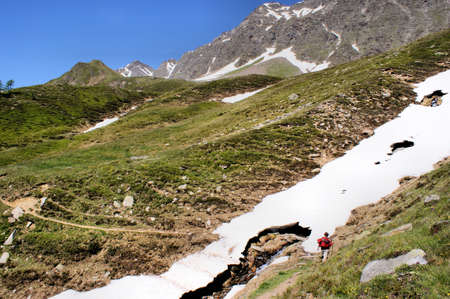 Mountain hiking in spring; a hiker in front of a thin snow field; rocks, steep slopes and deep blue sky  Stock Photo - 13774897