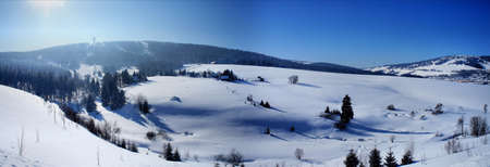 erzgebirge: Panorama of the Bohemian Erzgebirge; idyllic winter landscape with single trees and huts; mountain and valleys; cloudless sky; panorama image