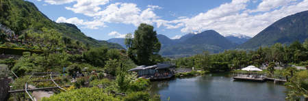 Panorama of the Botanical Garden Trauttmansdorff Castle in Merano, Italy; in the background snow-capped mountains and valleys; in the foreground Mediterranean vegetation and the water lily pond; blue sky with some white clouds Фото со стока