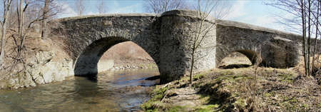 gro: Imposing stone arch bridge over the Great Striegis in Saxony, Germany; barren landscape in spring, bare meadows and trees, blue sky with white clouds, panoramic image Stock Photo