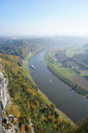 attraktion: View from the Bastei on the Elbe; colorful deciduous forests, sunny day