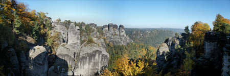 attraktion: View from the Bastei on the bizarre rocks of the Saxon Switzerland in Germany; colorful autumn forests and blue sky