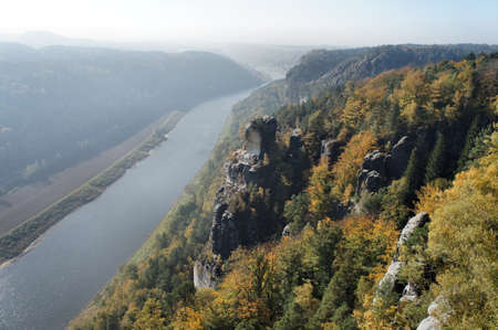 downstream: View from the Bastei-Bridge in Saxon Switzerland in Germany on the Elbe River downstream; a sunny autumn day; backlit subject;
