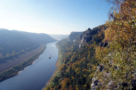 downstream: View from the Bastei-Bridge in Saxon Switzerland in Germany on the Elbe River downstream, a sunny autumn day, backlit subject,