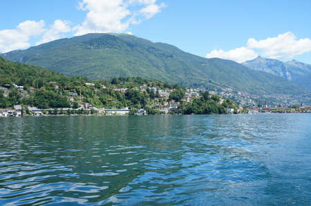 forested: On Lake Maggiore in Ticino, Switzerland; small towns, houses and forested mountains; in the foreground the lake; blue sky with white clouds