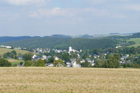 late summer: View of a village in the Erzgebirge; it s late summer, in the foreground a ripe grain field; hilly landscape with woods and fields; Stock Photo