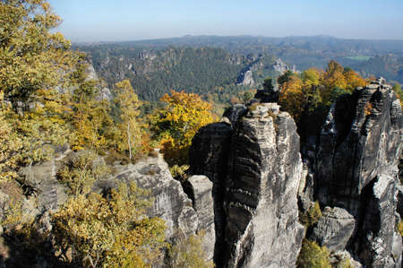 attraktion: Rocks, colorful trees and blue sky in the German part of the Elbe Sandstone Mountains in Germany