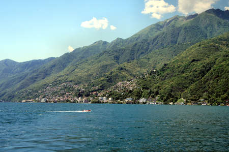 forested: On Lake Maggiore in Ticino, Switzerland; small towns, houses and forested mountains; in the foreground a boat on the lake; blue sky with white clouds Stock Photo