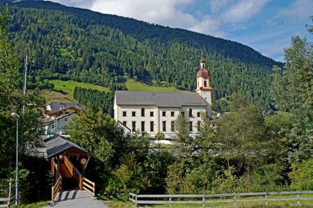 forested: A striking church in the Stubai Valley in Tyrol, a roofed wooden bridge and forested mountains