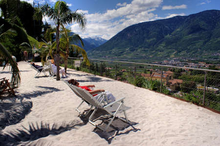 botanical gardens: In the Botanical Gardens of Merano people lying in lounge chairs under palm trees, views of the Adige Valley and the mountains of South Tyrol, blue sky with white clouds