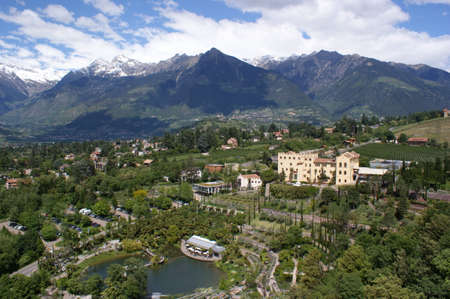 bird s eye: View from the bird s eye on the Botanical Gardens Trauttmansdorff and parts of Merano in South Tyrol, in the background Tirolo and the snow-capped peaks of the Texel Group Stock Photo