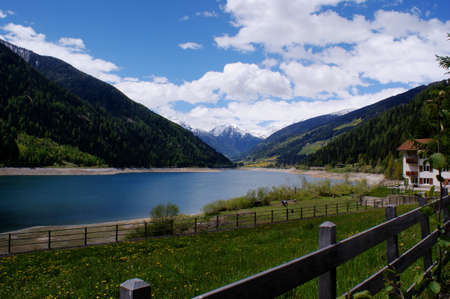 dandelion snow: The Zoggler-dam lake in the Ultental in South Tyrol, Italy; in background snow-capped mountains; blue sky and white clouds; wonderful weather to hiking Stock Photo