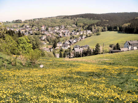 erzgebirge: Idyllic village in the Ore Mountains in Saxony, Germany; lush meadows with spring flowers; blue sky