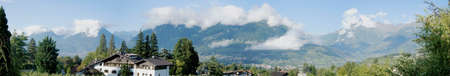 meran: Panoramic of the valley basin of Merano, South Tyrol, Italy; it s fall, blue sky and peaks in clouds, mountains and valleys, apple orchards between houses Stock Photo