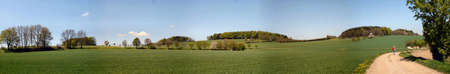 erzgebirge: Landscape in the Ore Mountains in Saxony, Germany; hiker on a hiking path through fields and forests in the spring, blue sky and white clouds; panoramic