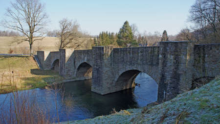 erzgebirge: Old stone bridge over the river Freiberger Mulde in the Ore Mountains in Middle Saxony, Germany; barren landscape in winter, blue sky Stock Photo