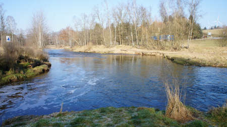 erzgebirge: A stream flows into the River Freiberger Mulde, barren nature on a sunny winter day, blue and cloudless sky, landscape in the Ore Mountains in Saxony Middle Stock Photo