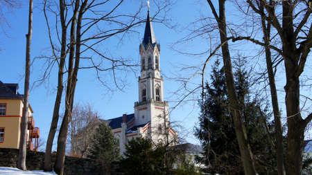 erzgebirge: View through trees soon on a church in the Ore Mountains in Saxony, Germany at a sunny winter day Stock Photo