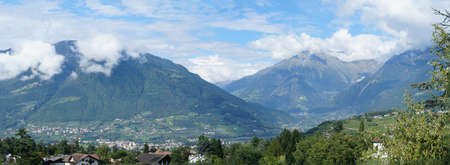 meran: Panoramic of the valley basin of Merano, South Tyrol, Italy; sunny day in summer, blue sky and peaks in clouds, mountains and valleys, villages in the Meran Country