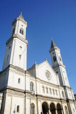 monument historical monument: Catholic Parish and University Church St. Louis in Munich, Sacred architecture style in arched, church with two towers, historical and architectural monument, cloudless blue sky and