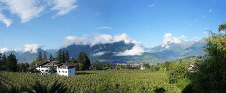 meran: Panoramic of the valley basin of Merano in South Tyrol, Italy; sunny day in summer, blue sky and clouds in peaks, mountains and valleys, houses between Apple Orchards