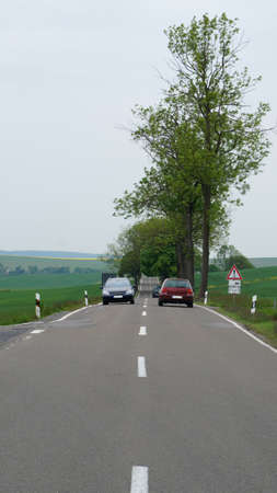 erzgebirge: Street in the Erzgebirge, two cars in the oncoming traffic Stock Photo