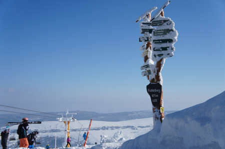 erzgebirge: thickly snow-covered and frost-covered Signposts on the Fichtelberg in the Ore Mountains in Saxony, Germany, overlooking the Bohemian part of the Erzgebirge in the Czech Republic