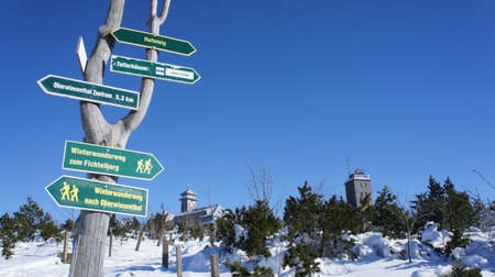 winter weather: Signposts on the Fichtelberg in winter, in the background the Fichtelberghaus and the weather station in the Erzgebirge in Saxony, Germany, sunny day and cloudless sky