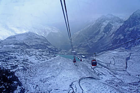 cable car: Cable car in the Stubai glacier area in Tyrol; landscape in high mountains and a cable car, day in late summer