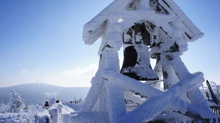 erzgebirge: Thick snow-covered Peace Bell on the Fichtelberg in the Ore Mountains in Saxony, Germany, in the background of Klinovec in the Bohemian part of the Ore Mountains, winter wonderland
