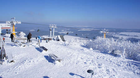 erzgebirge: Winter sports area on the Fichtelberg in the Ore Mountains in Saxony, Germany, Cable Car and chairlift, snow-capped landscape, view to Bohemia in the Czech Republic, blue sky